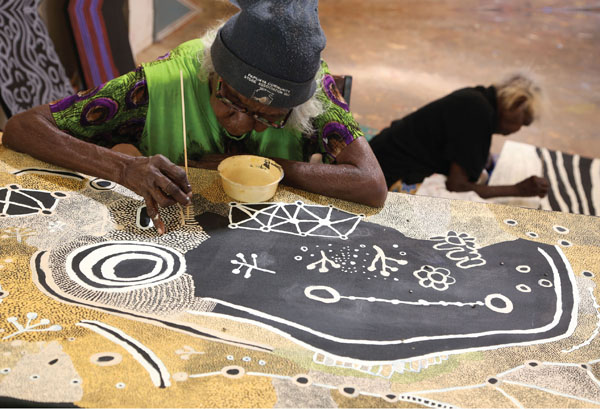 Martha McDonald Napaltjarri (in foreground) and Mona Nangala painting at Papunya Tjupi art centre, Papunya, 2015. Photo: Helen Puckey.